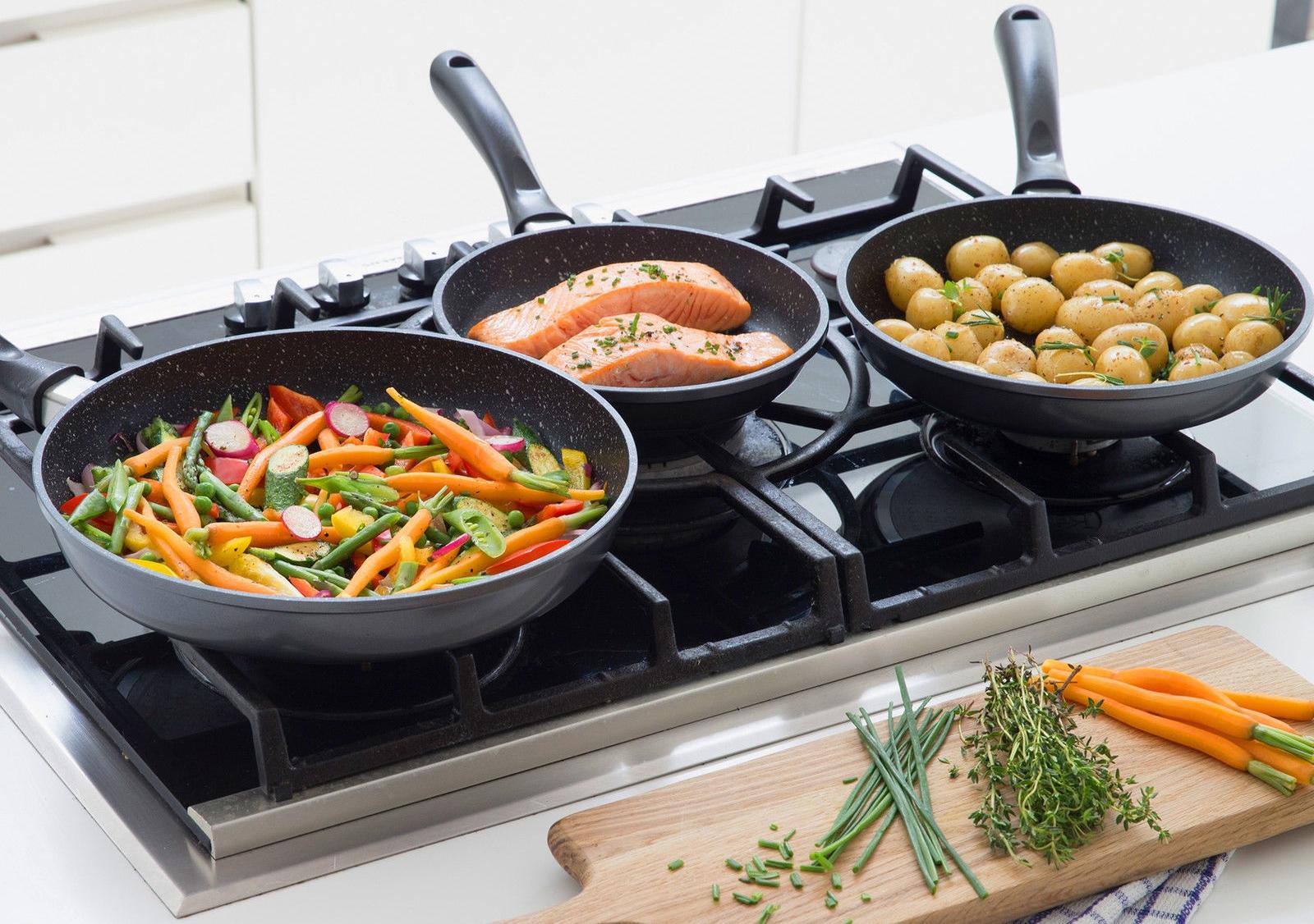 Сковороды с пищей на плите