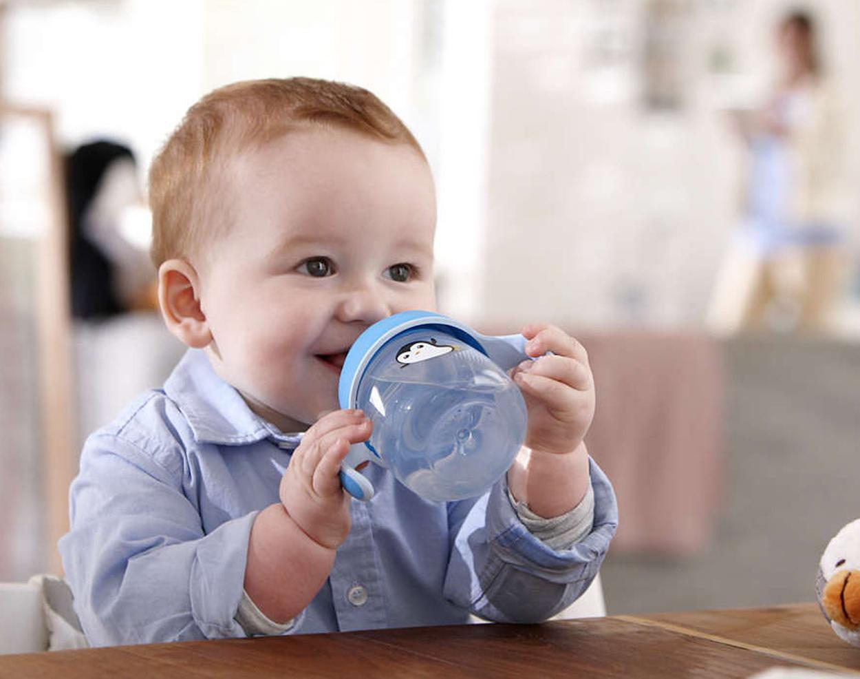 Малыш пьет из поильника