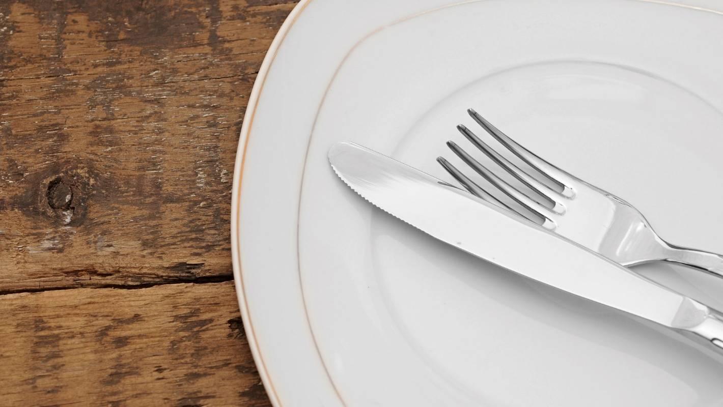 Нож с вилкой после еды на тарелке